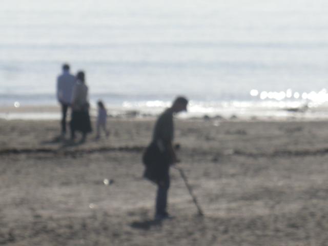 05) 消去せず、ピンボケにて このページでボツ写真供養をス。手前:金属探知機か?磁石探索機か?で砂浜を探索する人物を傍観したつもり・・・ でもピンボケで、ボツ写真合祀墓へ改